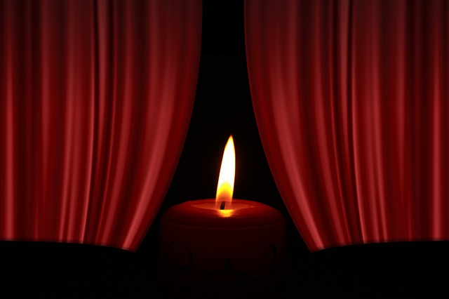 Brennende Kerze vor einem roten, sich öffnenden Vorhang